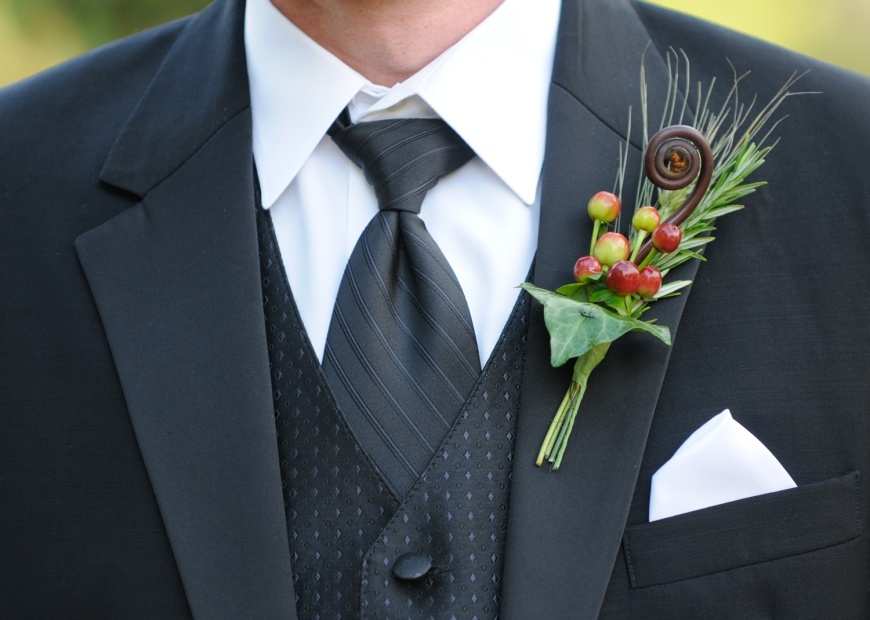 The modern groom, wearing a tuxedo accented by a fiddlehead fern and hypericum berry bout.